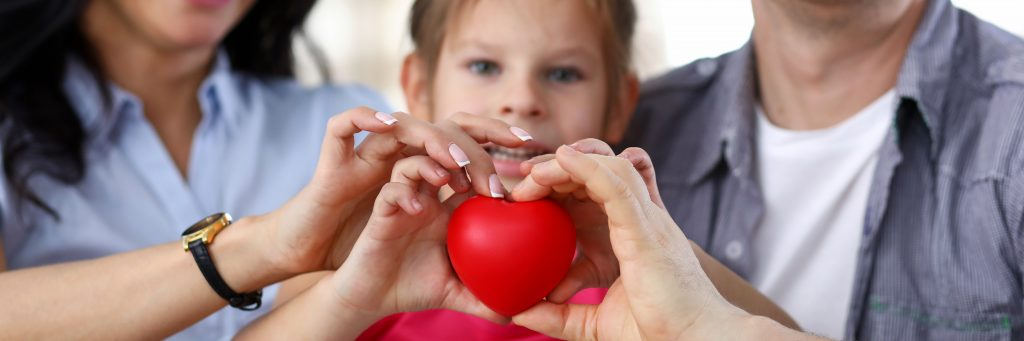 Child adoption. Family with adopted child holding heart toy.